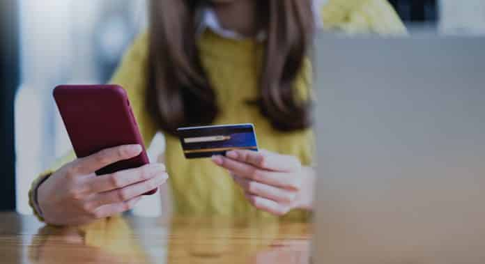 Young woman paying online by smartphone and credit card, Online shopping, Online banking.